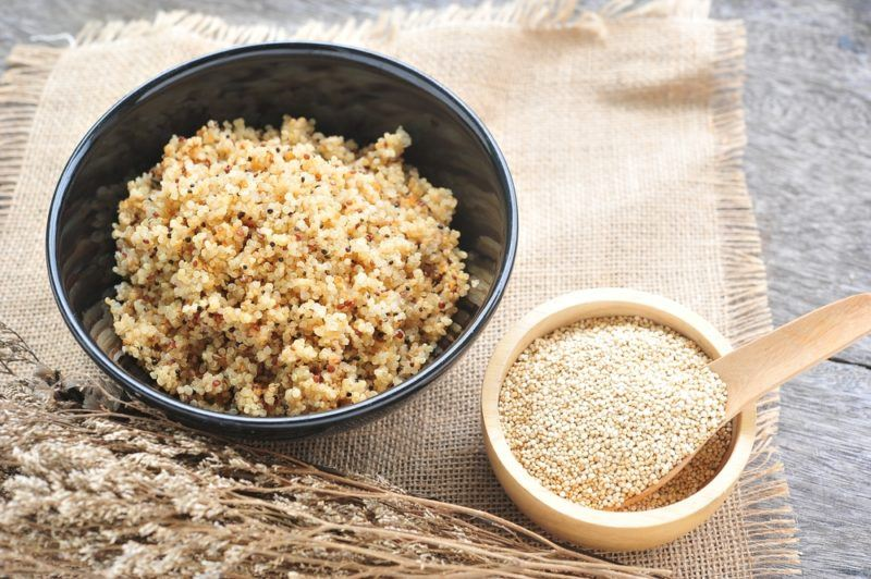 A dark gray bowl of cooked quinoa, with a smaller bowl of uncooked quinoa next to it