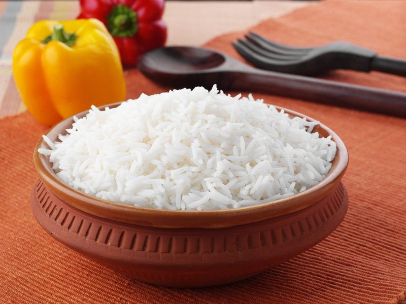 A terracotta dish of cooked rice, with peppers and cutlery in the background