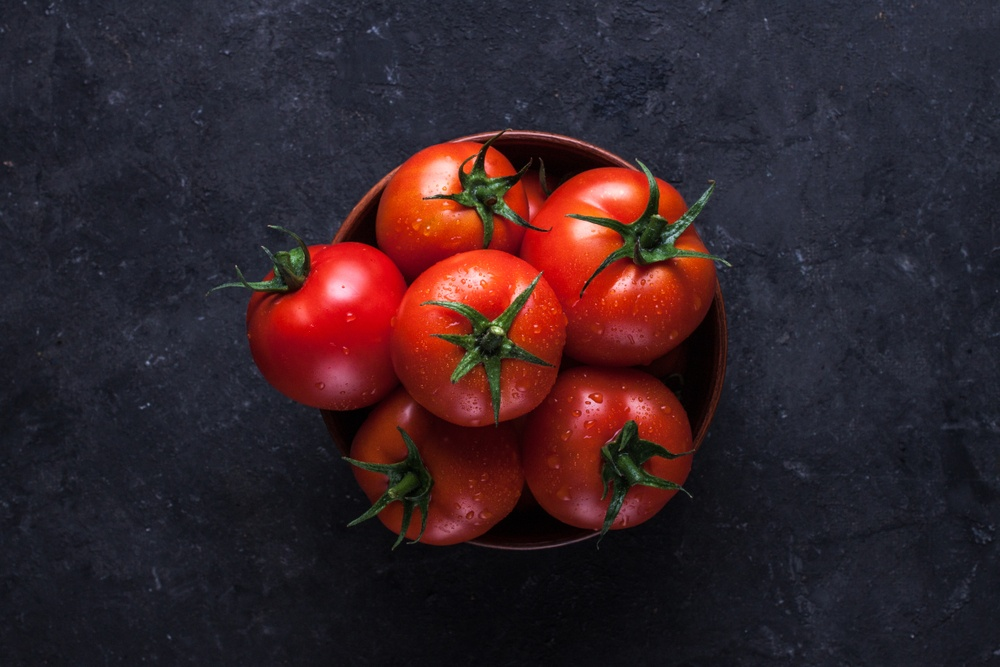 A small black bowl filled with fresh tomatoes