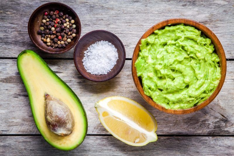 A bowl of guacamole, next to a lemon wedge, small bowls of salt and pepper, and half an avocado