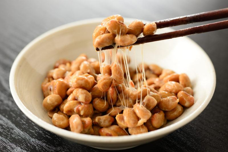 A bowl of natto soy beans with some being pulled out using chopsticks