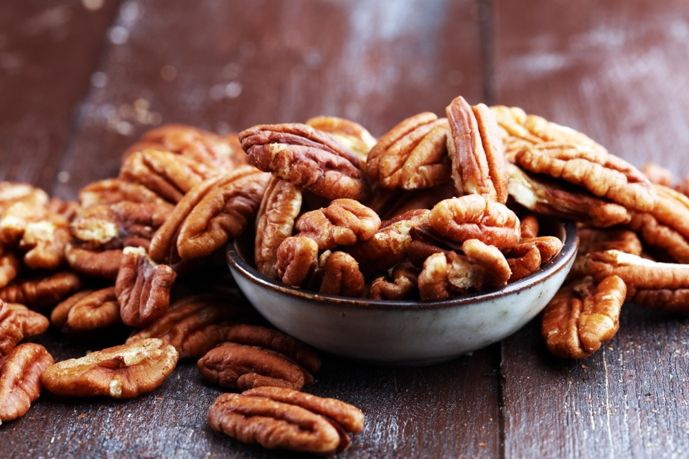 A bowl of pecans on a wooden table