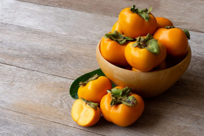A brown bowl with Fuyu persimmons
