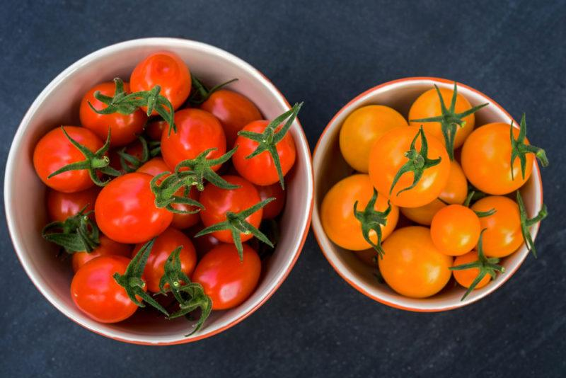 A bowl of red tomatoes and a bowl of yellow ones