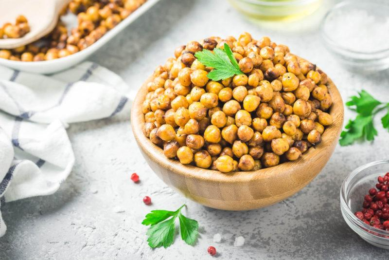A wooden bowl filled with roasted chickpeas