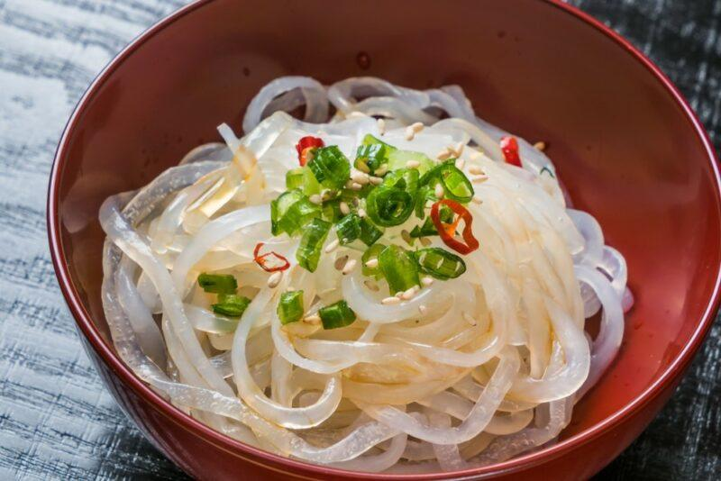 A red bowl of shirataki noodles with chives