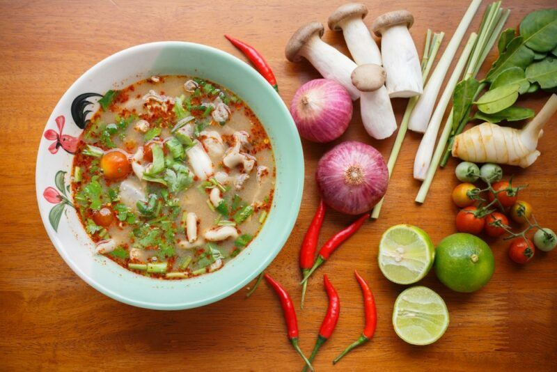 A blue green bowl containing a spicy tom yum soup, next to a selection of fresh ingredients