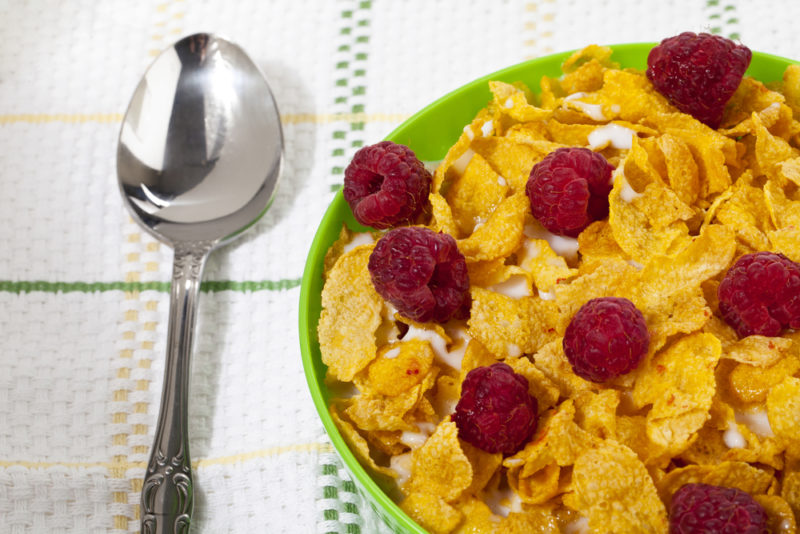 A green bowl with vitamin D fortified cornflakes, milk, and berries, next to a spoon on a tablecloth