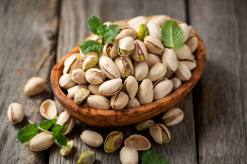 A brown bowl of fresh pistachio nuts with more on the table