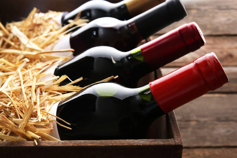 A wooden box with straw and bottles of merlot wines