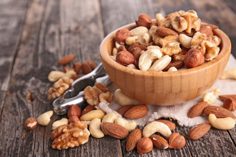 A wooden bowl of nuts, with more nuts on a table