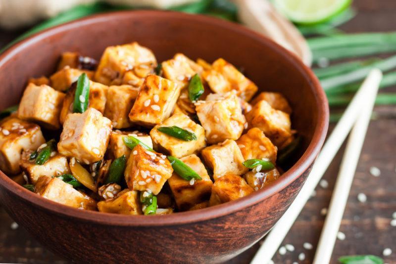 A dark brown bowl with tofu and greens, next to chopsticks