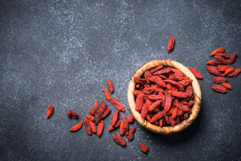 A top down image of a brown bowl of goji berries on a black background