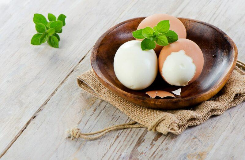 A brown bowl with three hard boiled eggs on a light wooden table