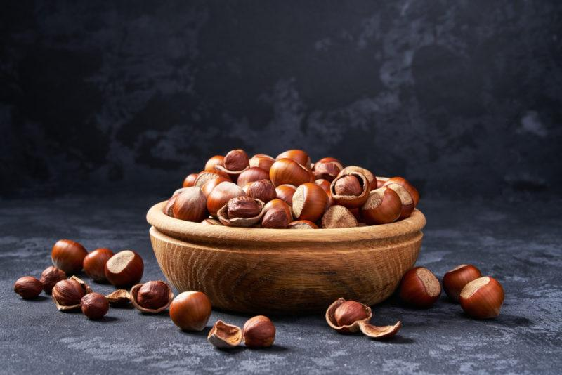 A brown wooden bowl piled high with hazelnuts, with more hazelnuts on the table itself