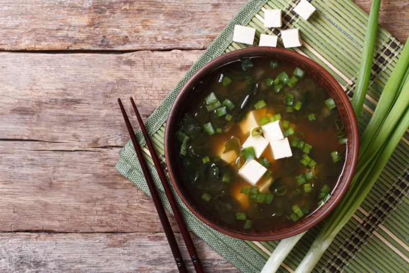 A brown bowl of fresh miso soup with tofu cubes, next to some spring onions, a pair of chopsticks and cubed tofu