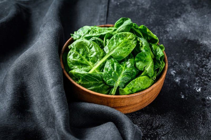 A wooden bowl of spinach leaves