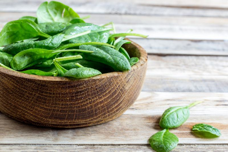 A brown wooden bowl of spinach on a table with a few leaves on the table too