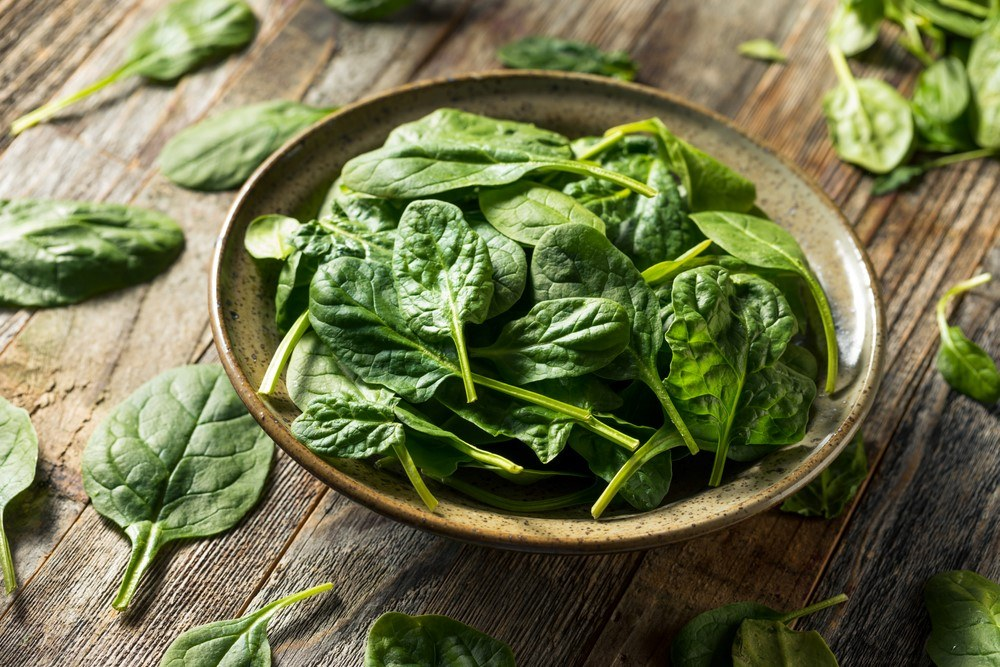 A ceramic bowl of spinach on a wooden table