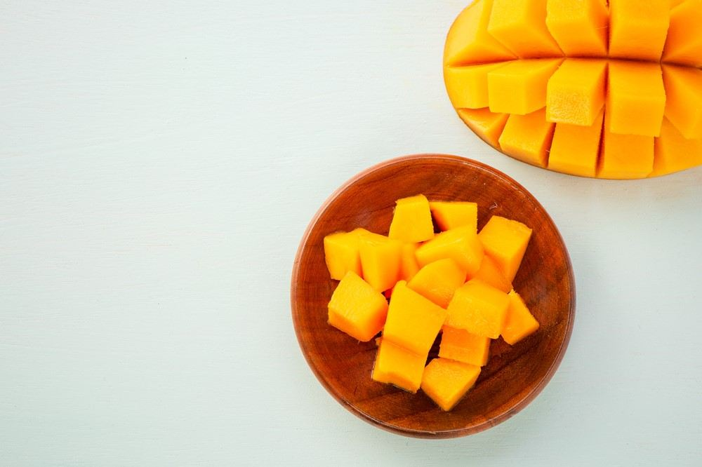 A brown bowl with mango pieces, next to half a mango