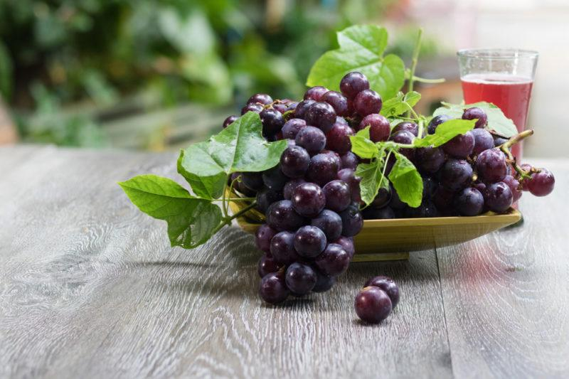 Dark grapes on a wooden plate