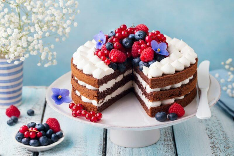A white cake stand with a layered cake topped with berries