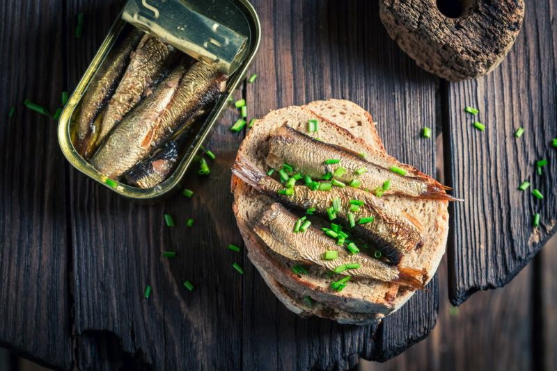 A can of sardines, next to sardines on a roll