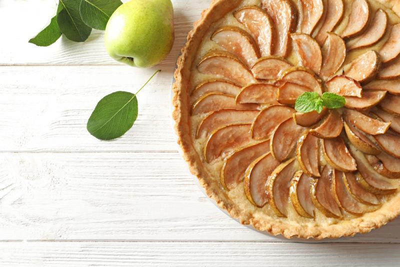 A dish of pear and caramel pie on a white deck or table with an apple or pear next to it