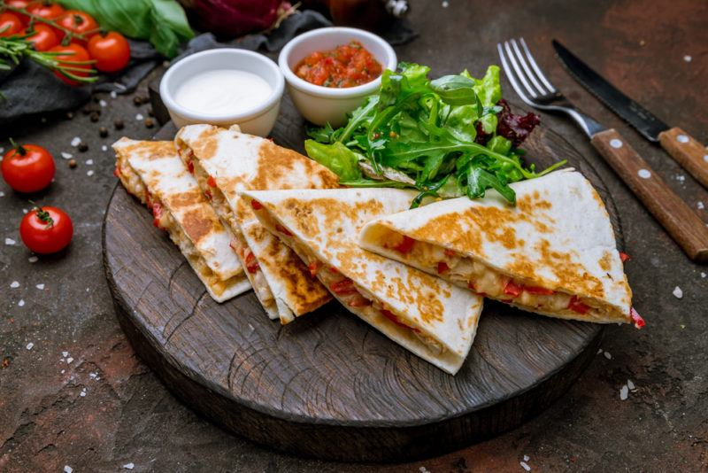 A wooden dish with quesadillas with dipping sauce and greens