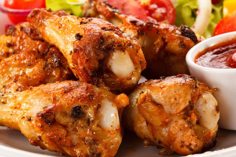 A close up image of chicken drumsticks for dinner next to some dipping sauce