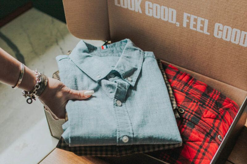 Someone unboxing clothing from Trendy Butler, showing shirt and text about feeling good
