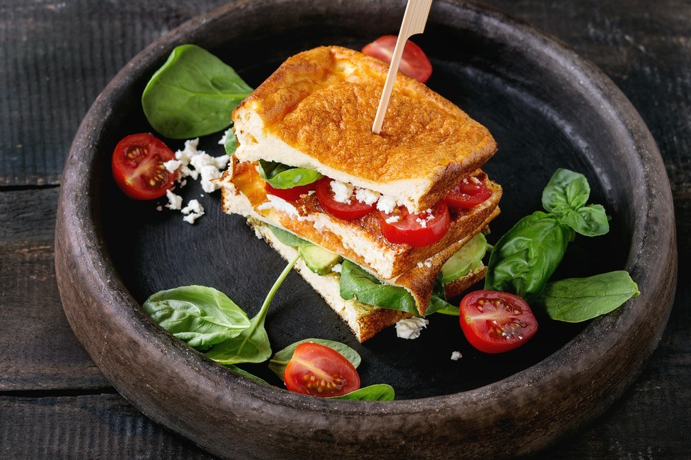 A dish that contains a sandwich made from cloud bread, along with spinach and tomatoes