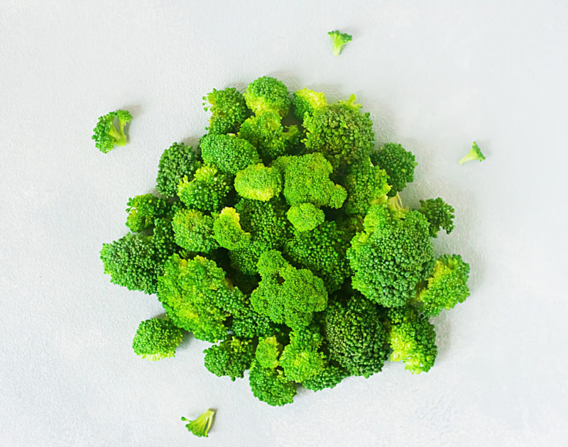 A clusber of bright green broccoli against a white background