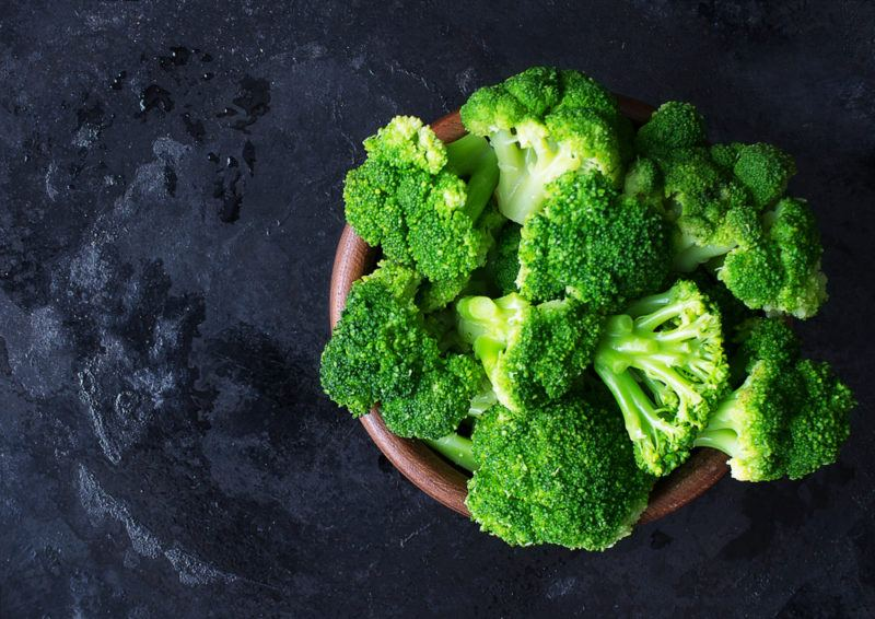 A wooden bowl containing bright green broccoli on a blue table