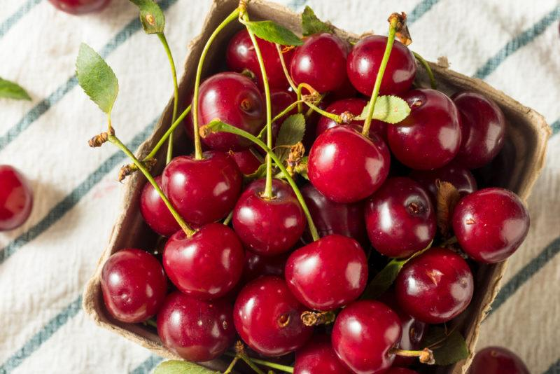 A wooden contain filled with a selection of tart cherries