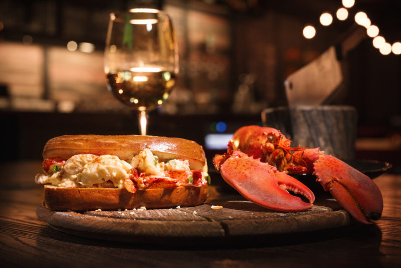 A lobster roll, a full lobster, and a glass of riesling in a restaurant
