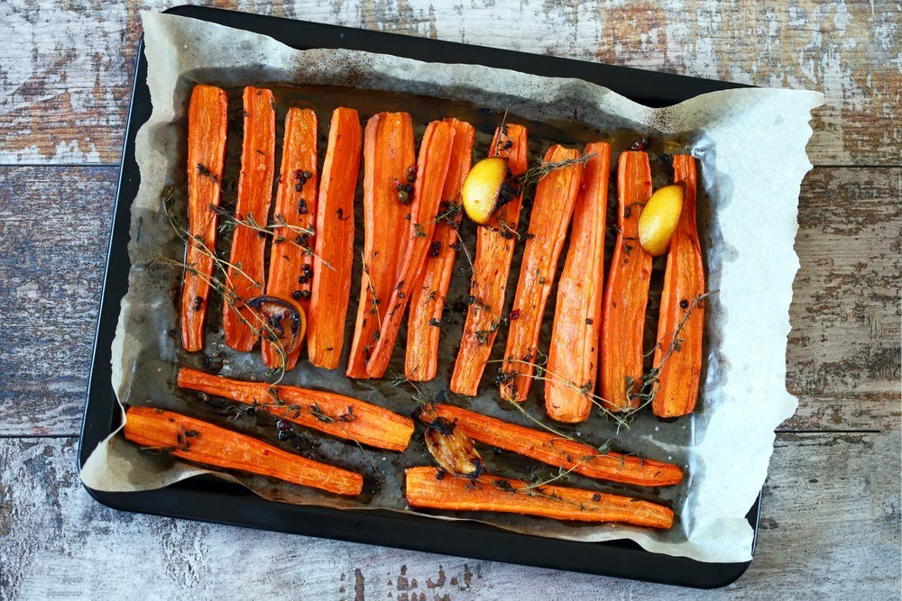 A baking tray with cooked carrot sticks with herbs