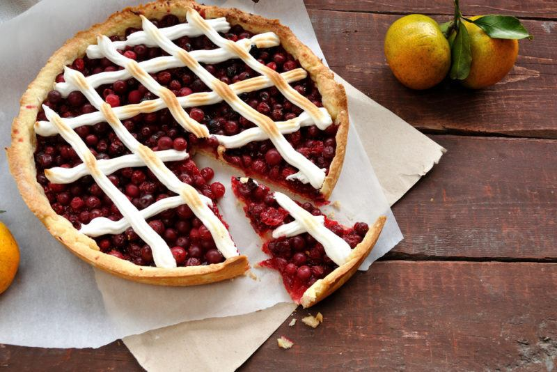 A cranberry pie with meringue lattice on pieces of paper with one piece of pie cut out of it