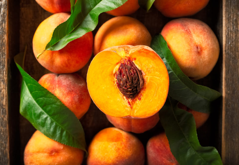 A crate of fresh peaches with leaves, one of which has been sliced in half