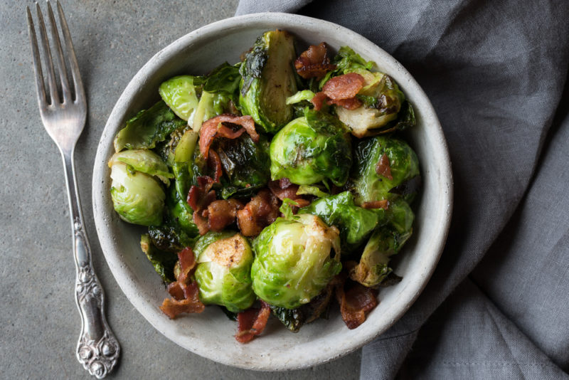 A white dish of Brussels sprouts with bacon