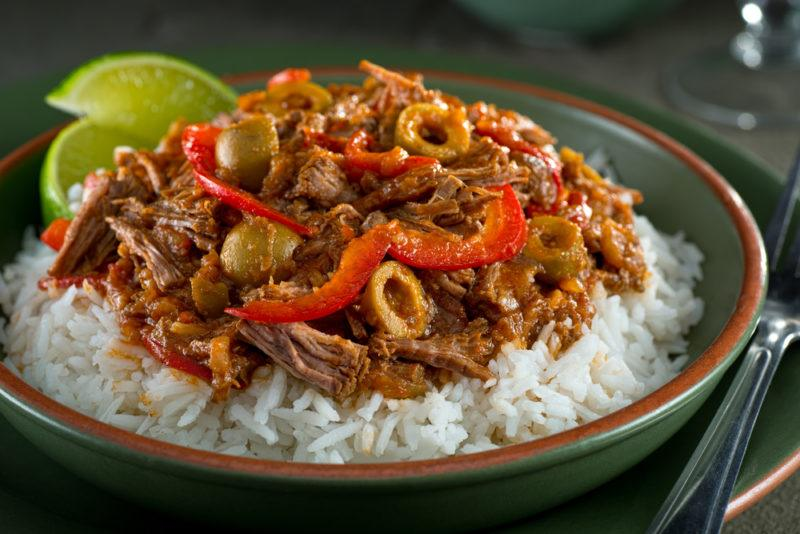 A green dish containing Ropa Vieja on rice