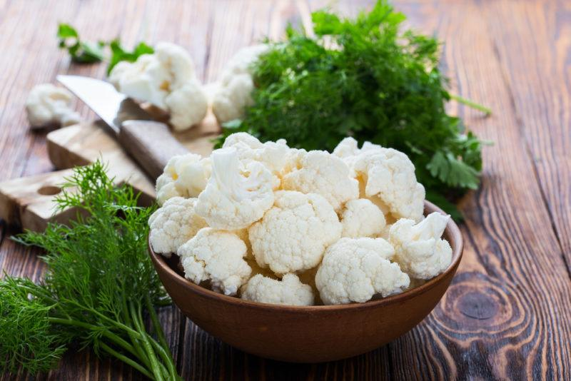 A brown dish of cauliflower on a wooden table, next to some leafy greens.