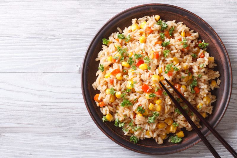 A brown bowl of fried rice with chopsticks