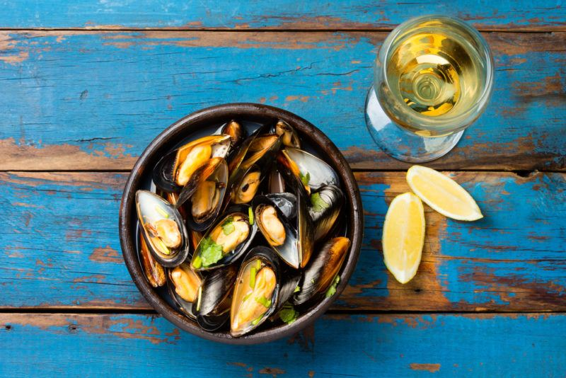 A black dish of mussels on a blue table next to lemon wedges and a glass of wine