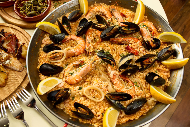 A dish of paella with lemon slices and seafood