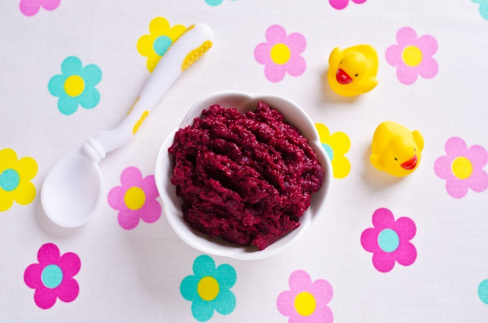 A white dish and spoon, where the dish contains purple baby food. There are flowers on the table cloth and a couple of plastic ducks.