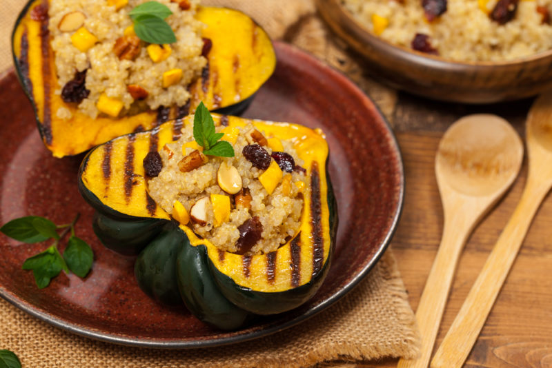 A brown-red dish containing an acorn squash that has been sliced in half, roasted, and stuffed, next to two spoons and a bowl of the stuffing