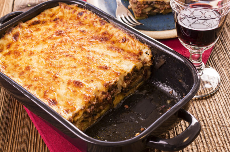 A deep dish that contains moussaka on a table next to a glass of red wine