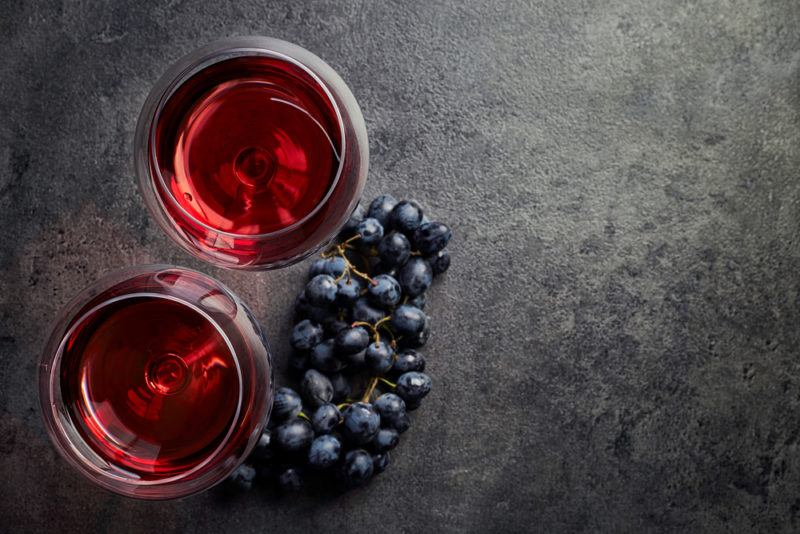 Two glasses of pinot noir and grapes on a gray table