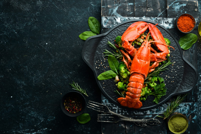 A top down image of a lobster on a bed of greens and a black tray